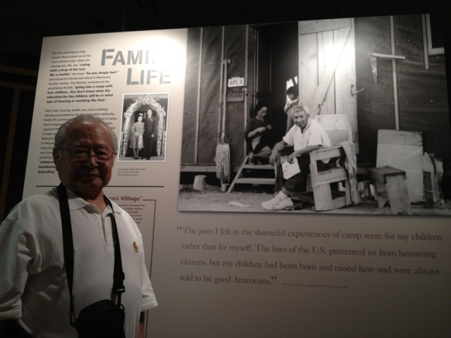 Victor Takemoto, who graduated from Manzanar High School in 1945,  stands in front of a photo of his parents and sister at the Manzanar Historic Site. (Photo Credit: J. Garfunkel)�